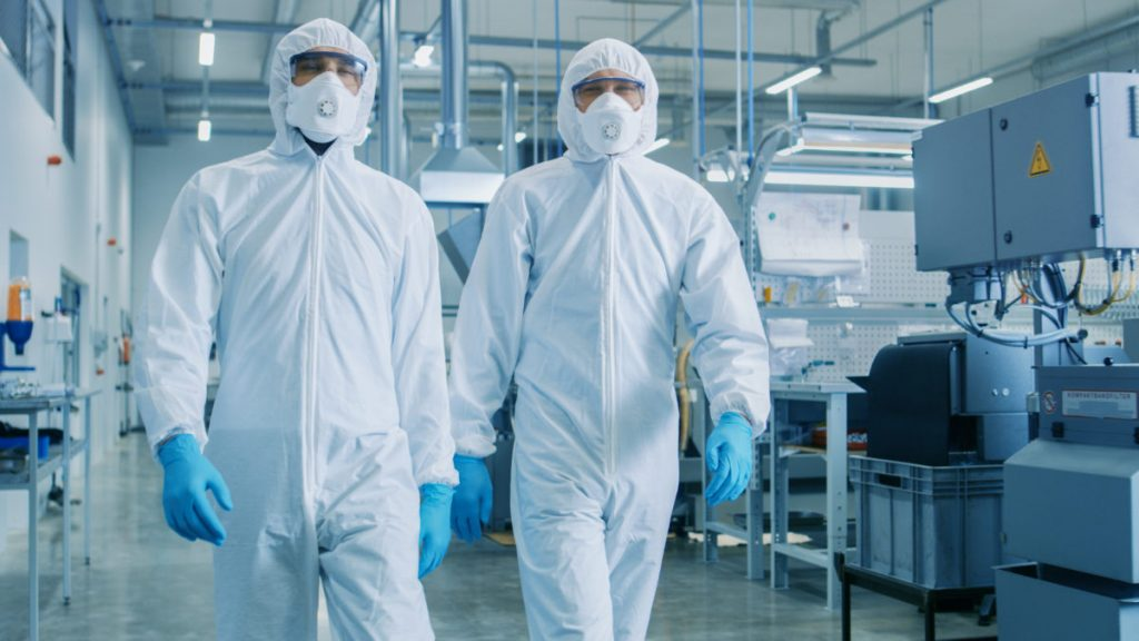 Two Engineers/ Scientists in Hazmat Sterile Suits Walking Through Technologically Advanced Factory/ Laboratory. Clean High-Tech Environment with CNC Machinery.